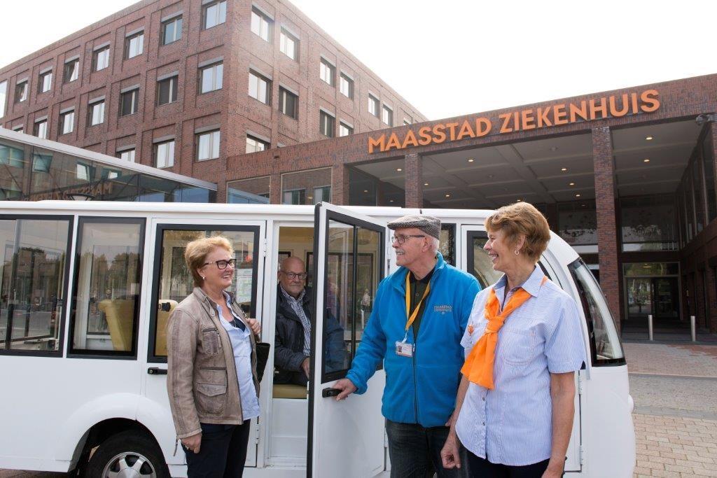 Vrijwilligers helpen mensen de bus in